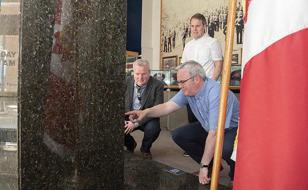 Three men near a monument
