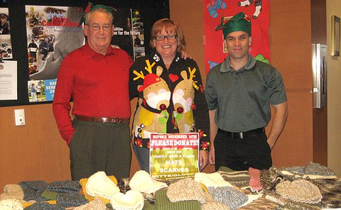 Two men and one women behind a table displaying knit toques