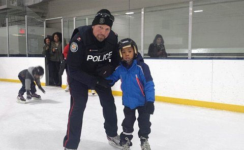 A boy being held by the arm by a man in TPS uniform on a rink