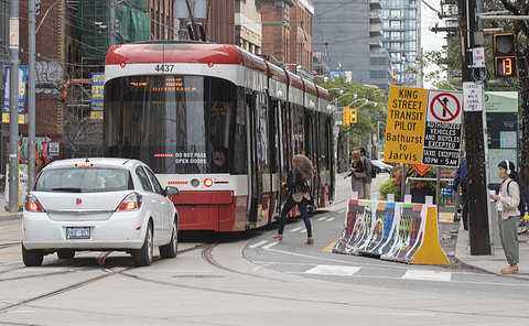 People get on streetcar at intersection