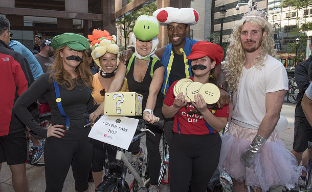 A group of people around a bike dressed any Super Mario characters