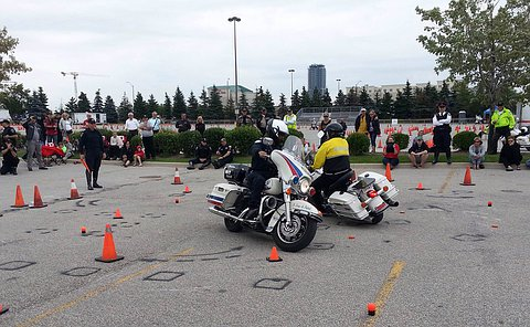 A man in TPS uniform on a motorcycle turning beside another man in uniform turning in the other direction close to one another surrounded by pylons and a few spectators