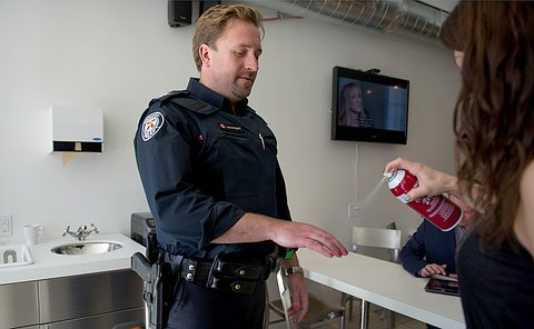 An officer holding his hand out as a woman sprays it to keep nail colour intact.