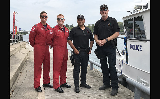 Two men in red jumpsuits with two men in TPS uniform beside a police boat