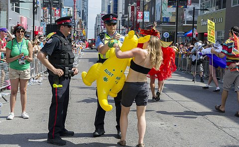 TPS Officer and Auxiliary Officer are engaging with a parade goer at the 2014 World Pride Parade. The parade goer is holding an inflatable Kangaroo (yellow in colour). Other parade goer's are walking around them.