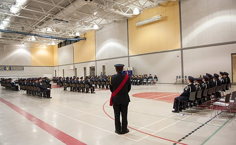 A wide angle shot of a graduation ceremony. Everyon is sitting.