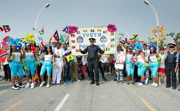 Many young people in festive gear with a police officer