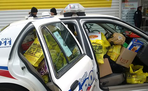 A Toronto police car with doors open filled with groceries in front and back seats