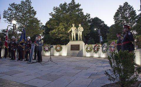A man in TPS uniform at a podium near a statue