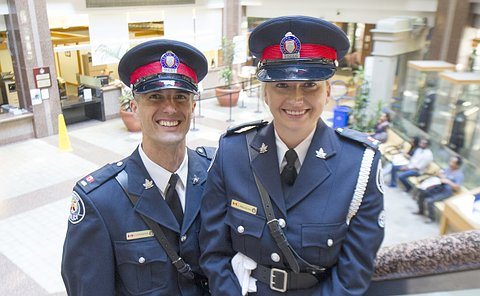 Man and a woman wearing police uniforms, standing on the stairs overlooking a lobby of a building