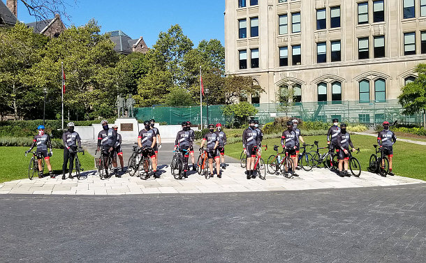A group of cyclists in front of a memorial
