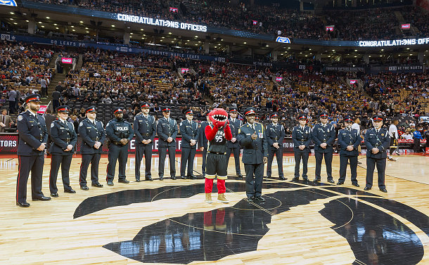 A group of men and women in TPS uniform on a basketball court with a dinosaur mascot