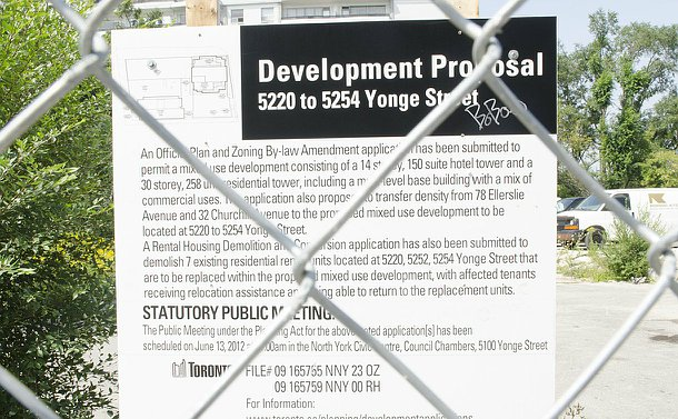 A proposed development sign on an empty paved lot behind a chain link fence