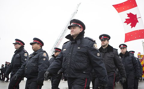 Men and women in uniform march as large Canadian flag hangs over them