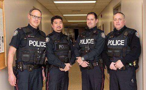 four men in uniform standing in a hallway