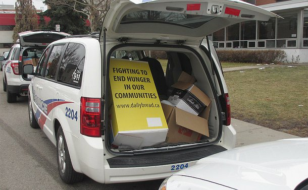Three TPS vehicles lined up, two with trunks open with boxes inside