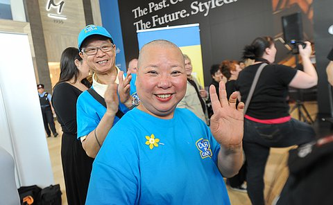 A man claps behind a woman with a shaved head in a cops for cancer T-shirt