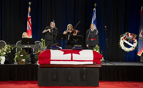 Four people on stage behind flag draped coffin. One is playing a keyboard, the next a flute, the next a violin and the last is a singer