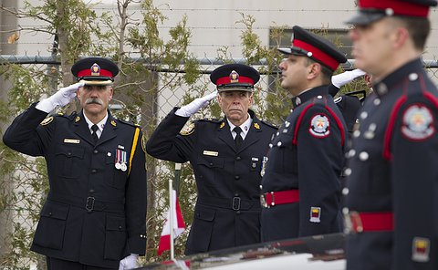 Two men in Toronto Police uniform salute and two other men in uniform flank the hood of a hearse