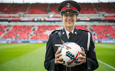 A woman in TPS uniform holding a soccer ball