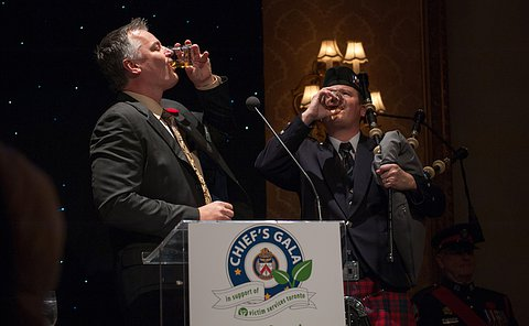 A man with bagpipes and a man in a suit taking a shot of alcohol as per traditional 'paying the piper' ceremony.