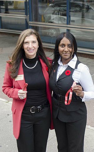 Two women stand together displaying red ribbons