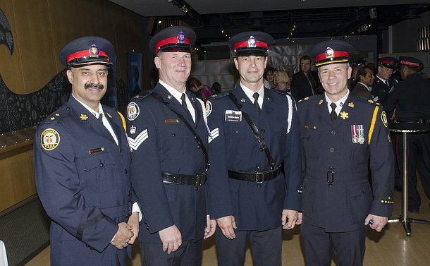 Four men in TPS uniform stand in a row