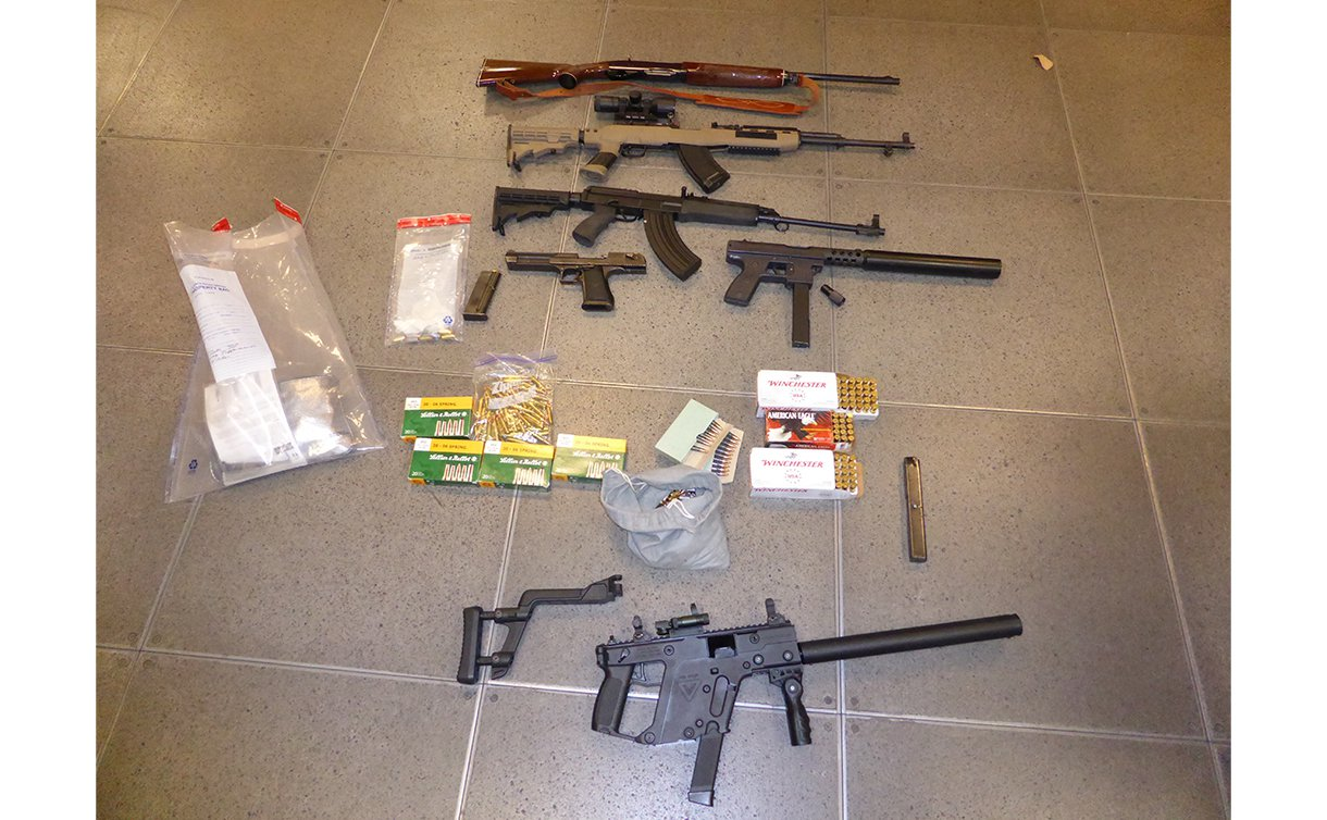 8 Guns laid out on a floor