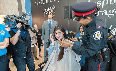 A cameraman man films as a woman in a TPS uniform holds a ponytail in front of a girl