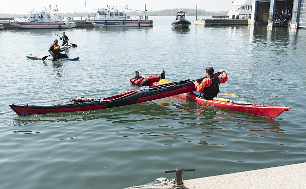 One man in a kayak, another holds on