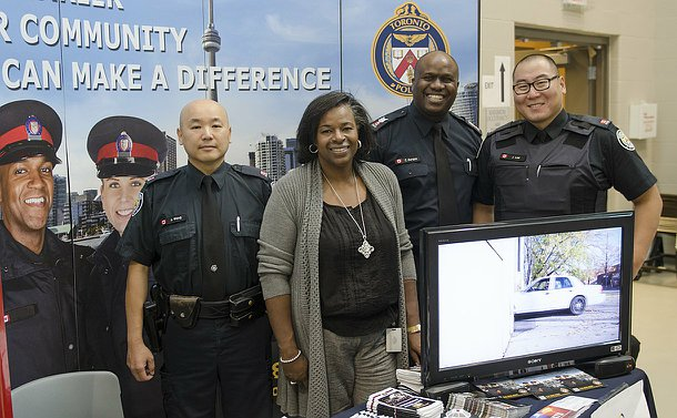 Three men in uniform with a woman behind a table and in front of a display featuring TPS crests and images of officers