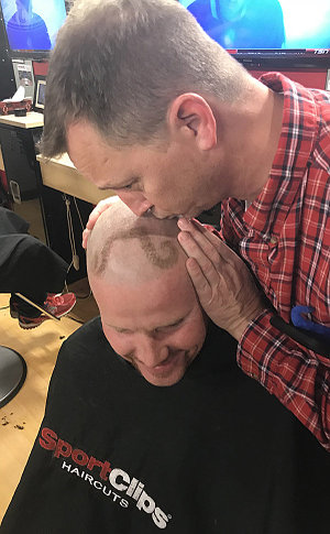 A man kisses another on his head