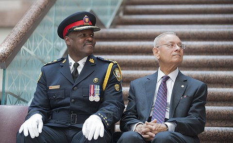 A man in TPS uniform sits beside another man