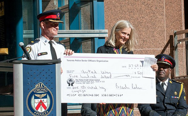 A man in TPS uniform holds a large cheque alongside a woman