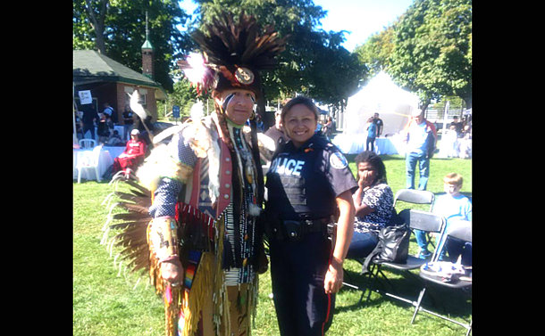 A woman in TPS unfiorm with a man in First Nations regalia