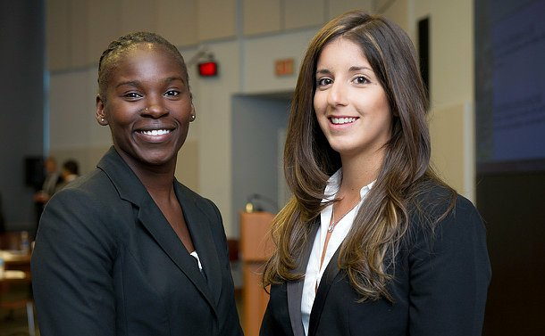 Two girls in suits, looking into the camera smiling.