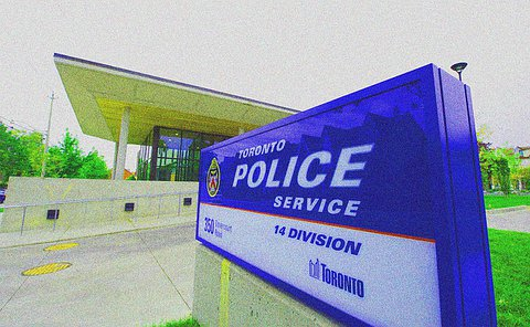 A Toronto Police 14 Division sign in the foreground and building in the background