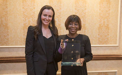 Two women stand together, one holding glass award