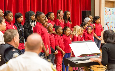 A woman seated at a piano in front of a group of girls in the same red golf shirt