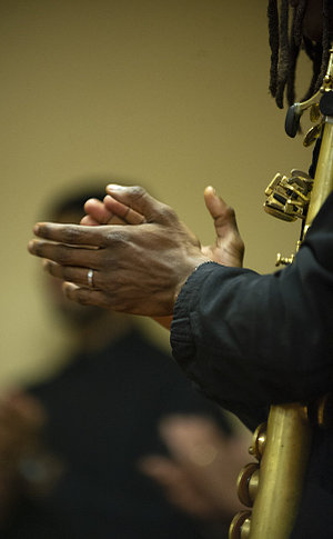 Hands clapping in front of a saxophone