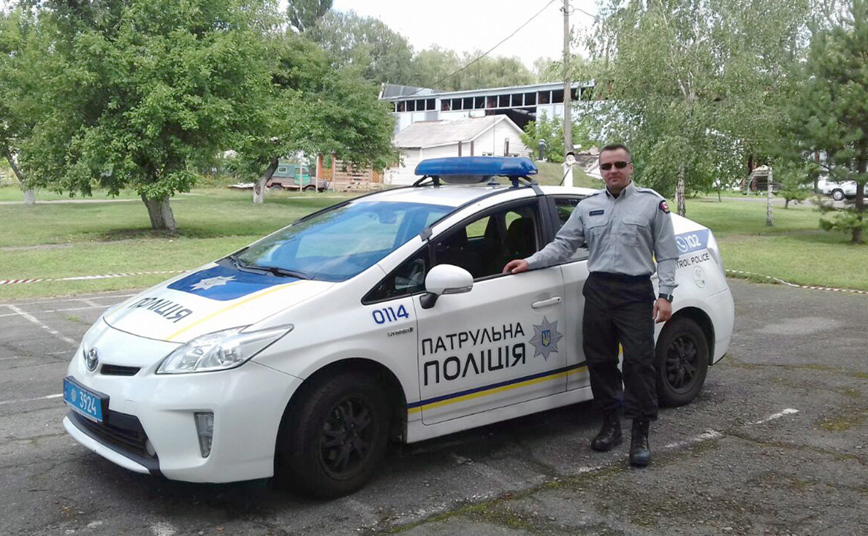 A man in police uniform beside a police car