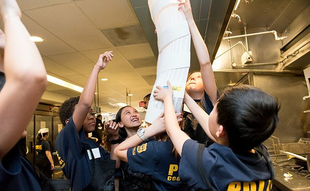 Students piling up chef hats on top of other chef hats to create a chef hat tower