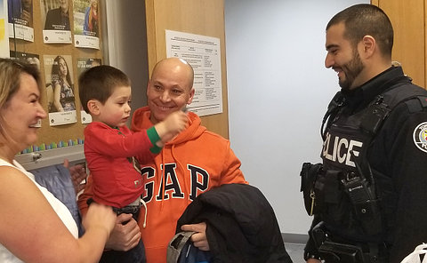 A man in TPS uniform with a couple holding a child