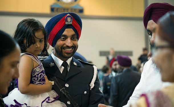A man in uniform holding a toddler in his arms and smiling near others