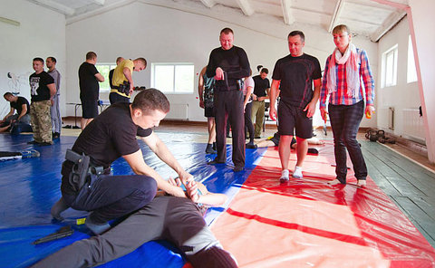 a man handcuffs another man on a floor with mats as three people look on