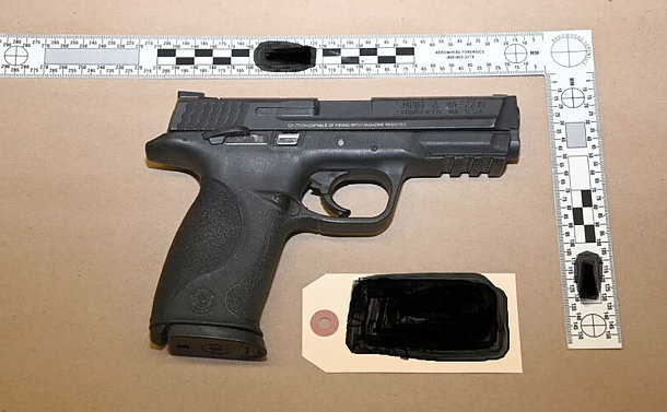 A black handgun beside a ruler