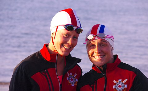 Two women in matching jackets wearing swim caps and goggles