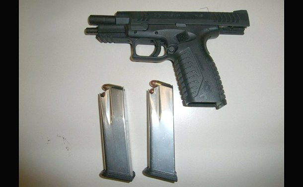 A black gun and two clips on a table