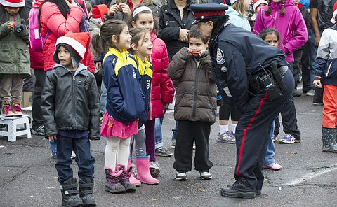 A woman in uniform leans over to speak to a group of four children