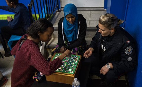 Two girls play a board game with a woman in TPS uniform